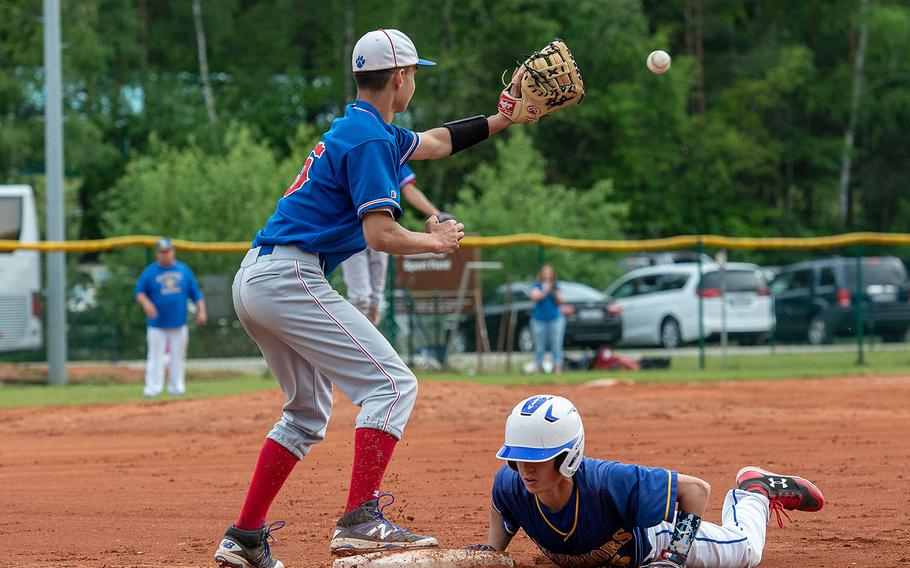 Wiesbaden's Robert Kennedy slides back into first base after a caught fly ball during a game against Ramstein on Day 2 of the boys Division I DODEA-Europe baseball championships, Friday, May 24, 2019.