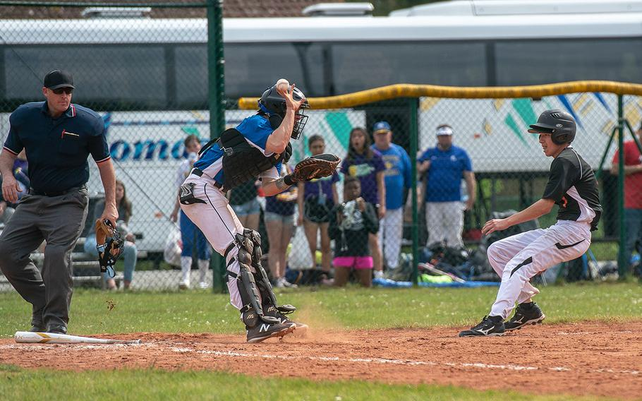 Hohenfels catcher Mitchell Darby loses the ball as Spangdahlem's Kayler Lobre comes home during a game on Day 2 of the boys Division II/III DODEA-Europe baseball championships, Friday, May 24, 2019.