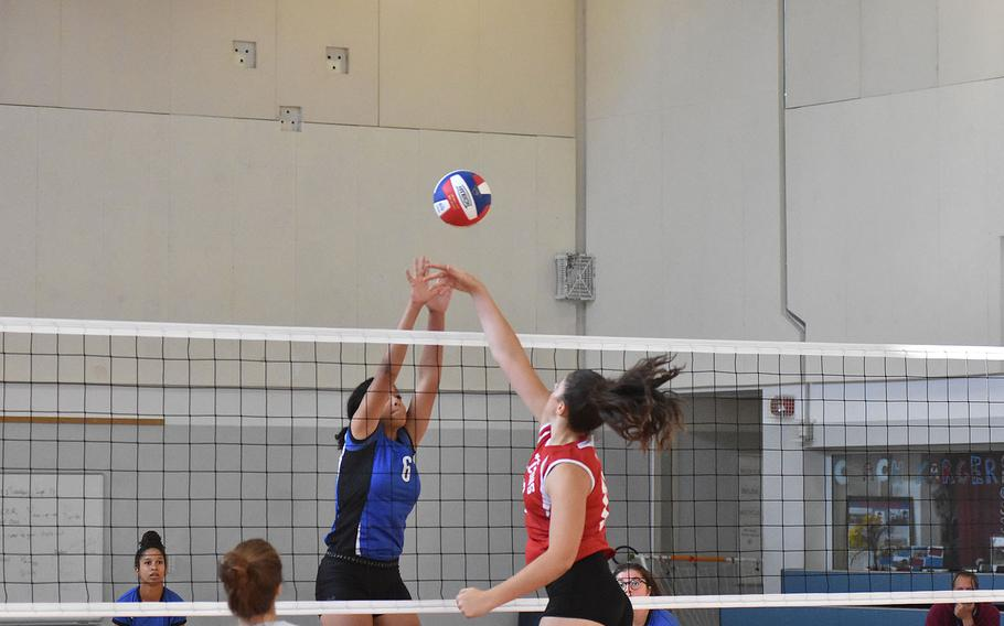 In a rare meeting at the net Saturday, Rota's Sydney Carroll and American Overseas School of Rome's Elizabeth Rogato square off for the ball.