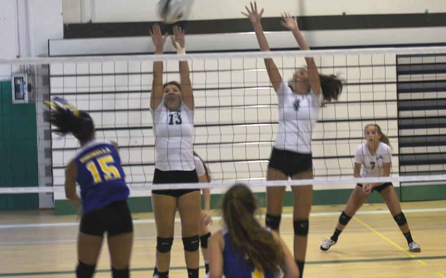 Naples Wildcat Fiona O'Connor jumps up to block an attempted kill by Jaguar Averi Chandler during a five-game match that Sigonella won on Saturday Sept. 14, 2019 at Naples Middle High School.