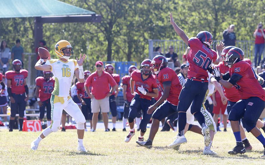 Matthew Owen, quarterback for the SHAPE Spartans, winds back to throw a pass during the Aviano Saints' 52-16 victory on Saturday, Sept. 21, 2019.