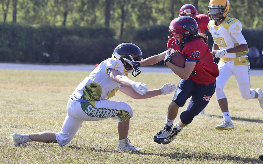 Jace Boren, a wide receiver for the Aviano Saints, tries to break away from a SHAPE defender during the game Saturday, Sept. 21, 2019.