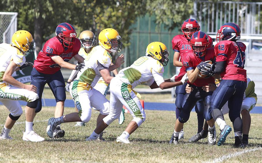 The SHAPE Spartans attempt to stop Aviano Saints wide receiver Jace Boren during the Saints' 52-16 victory over the Spartans on Saturday, Sept. 21, 2019.