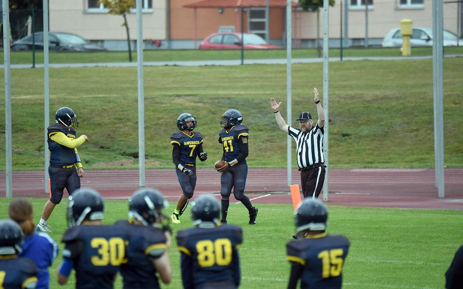 The referee puts his hands up as Cougar Devin Jenkins scores one of his several touchdowns in a game against Brussels, at Ansbach, Germany, Friday, Sept. 27, 2019.