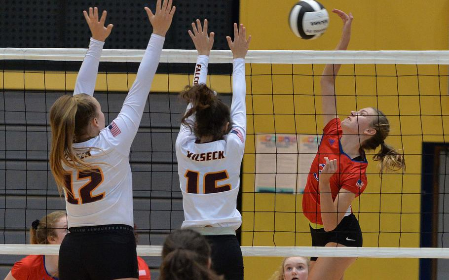 Ramstein's Giselle Stake hits the ball against Vilseck defenders Rebekah Heckert and Reyne Drasny in a Division I semifinal at the DODEA-Europe volleyball finals in Ramstein, Friday, Nov. 1, 2019.  Ramstein won 25-21, 25-20, 25-20 and will face Stuttgart in Saturday's final.