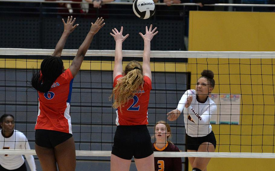 Vilseck's Kayla Silva slams the ball over the net past the Ramstein defense of Tamiya Bruce and Isabella Coddington in a Division I semifinal at the DODEA-Europe volleyball finals in Ramstein, Friday, Nov. 1, 2019.  Ramstein won 25-21, 25-20, 25-20 and will face Stuttgart in Saturday's final.