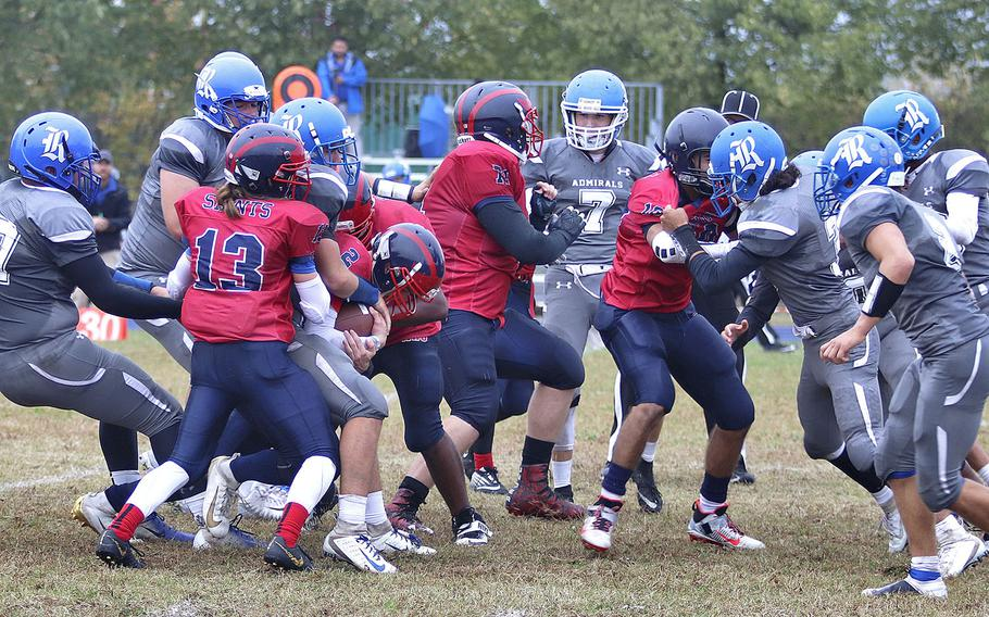 Aviano Saints quarterback Michael Hauser fights to gain yardage as Rota Admirals defenders try to bring him down during Saturday's DODEA-Europe Division II Championship game held at Aviano.