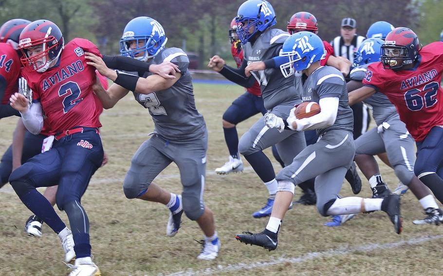 Rota Admirals running back Judge Tice attempts to break away from Aviano Saints defenders during Saturday's DODEA-Europe Division II Championship game held at Aviano.