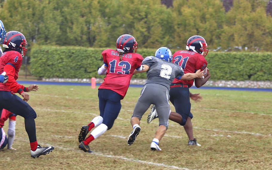 Aviano Saints fullback Raymond Harden breaks away from Rota Admirals defenders on his way to scoring a touchdown during Saturday's DODEA-Europe Division II Championship game held at Aviano.  The Saints defeated the Admirals 16-7 and with the win, they secured back-to-back championships.