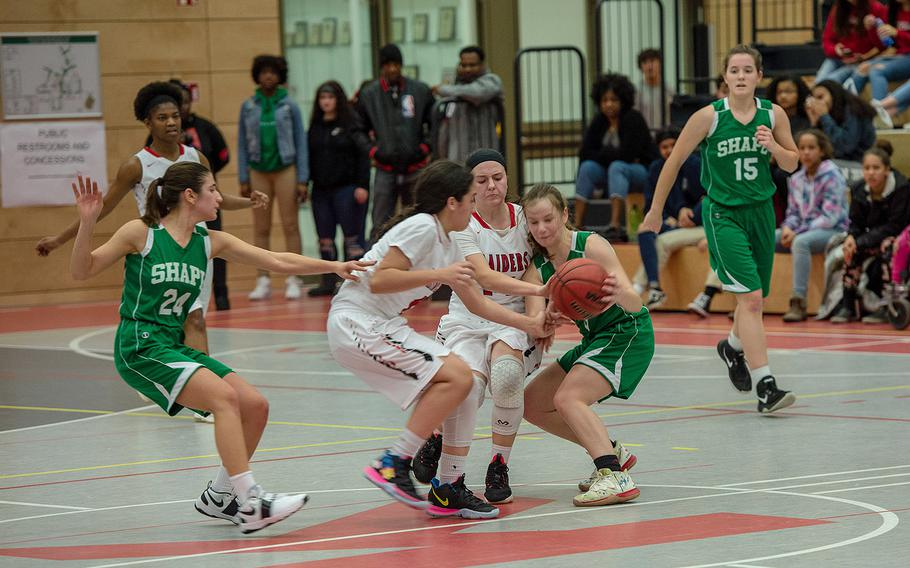 Players battle for the ball during a basketball game between SHAPE and Kaiserslautern at Kaiserslautern High School, Germany, Friday, Dec. 6, 2019. SHAPE won the game 45-40.