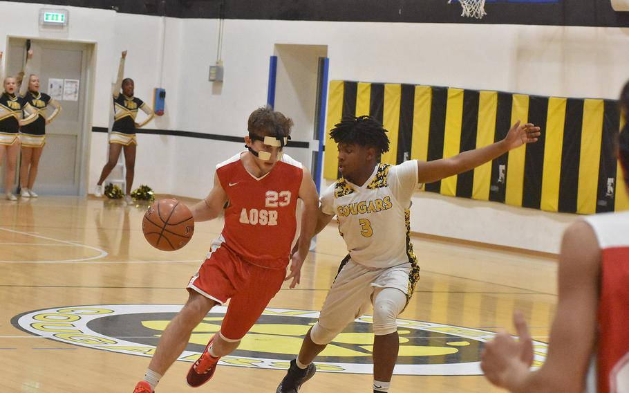 American Overseas School of Rome's Niv Eshel drives against Vicenza's Zach Cohen on Friday, Dec. 6, 2019. The Falcons topped the Cougars 61-48.