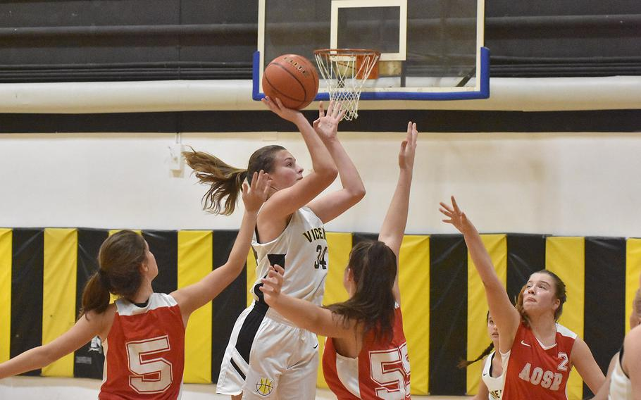 Vicenza's Claire Troiano puts up a shot while surrounded by Ameircan Overseas School of Rome defenders in the Cougars' 41-33 victory on Friday, Dec. 6, 2019.
