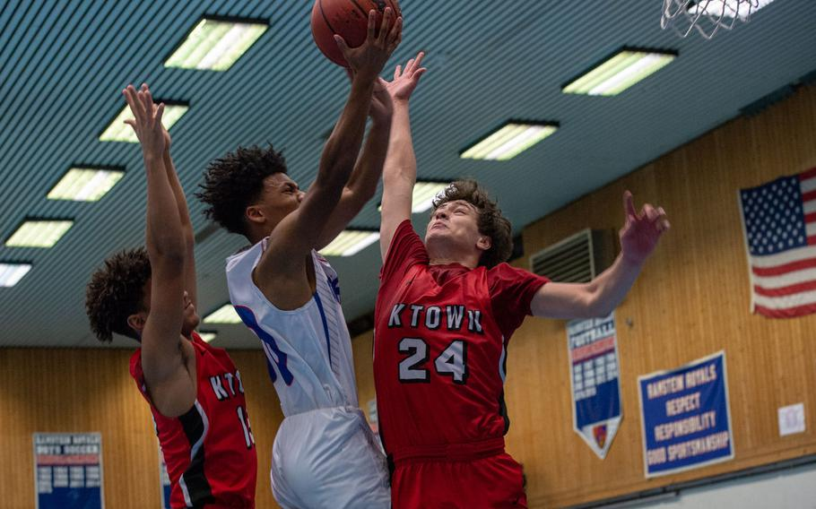 Ramstein's Jerod Little drives to the basket as Kaiserslautern's Isaak Pacheco goes up for the block during a basketball game at Ramstein High School, Germany, Dec. 17, 2019. Ramstein won the game 72-56.