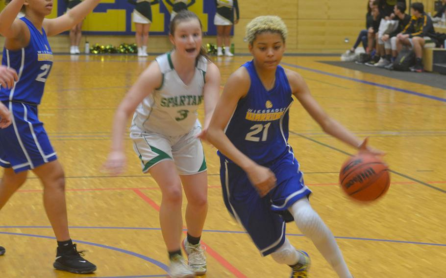 Wiesbaden's Alynna Palacios dribbles past SHAPE defenders. The Spartans beat the Warriors 40-26.