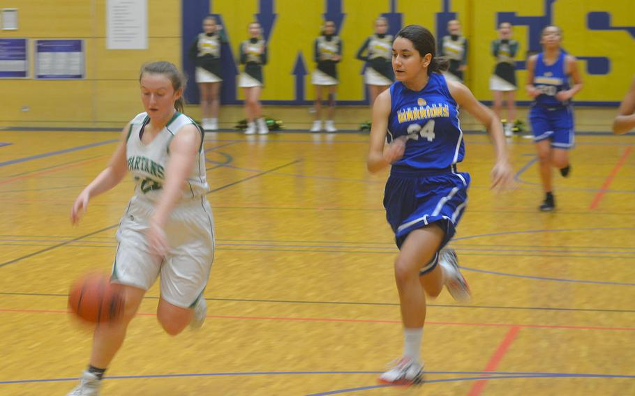 SHAPE's Gabi Shultz drives the ball past Wiesbaden defenders. The Spartans beat the Warriors 40-26.
