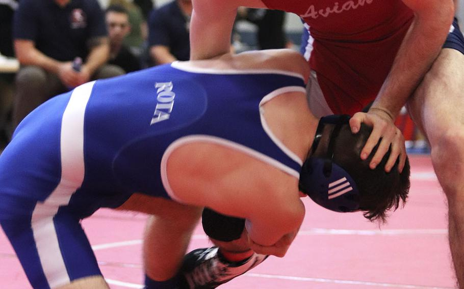 Michael Hauser of the Aviano Saints defends against Rota Admirals' Jordan Cookerly in the 145-pound weight class matchup of Saturday's wrestling sectional held at Aviano, Italy. Hauser won the match by pin and finished the day in first place.