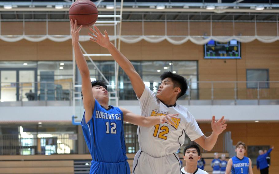 Robin Kim of Hohenfels shoots over Baumholder's Isaiah Daep in a Division III semifinal at the DODEA-Europe basketball championships in Wiesbaden, Germany, Friday, Feb. 21, 2020. Baumholder beat Hohenfels 73-58 to advance to the finals.