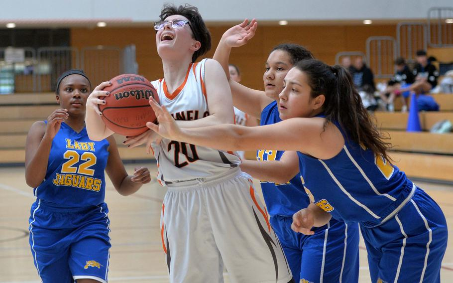 Lorelai Vargo of Spangdahlem is stopped by Katie Payne of Sigonella with a foul as Shanyah Kentish, left, and Jocelyn Harris watch. The Sentinels advanced to the Division III finals with a 39-14 win at the DODEA-Europe basketball championships in Wiesbaden, Germany, Friday, Feb. 21, 2020.