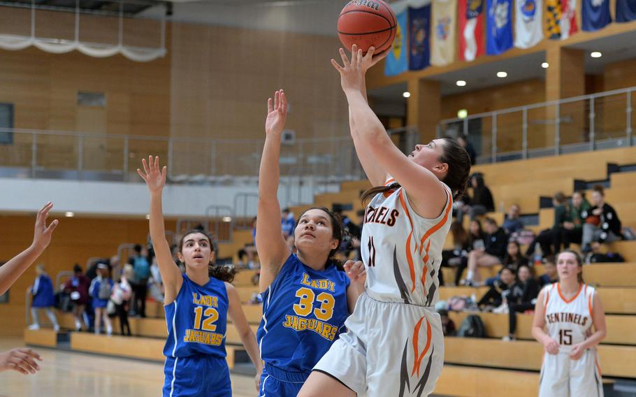 Izzy Smith of Spangdahlem shoots as Sigonella's Jocelyn Harris defends. The Sentinels advanced to the Division III finals with a 39-14 win at the DODEA-Europe basketball championships in Wiesbaden, Germany, Friday, Feb. 21, 2020.