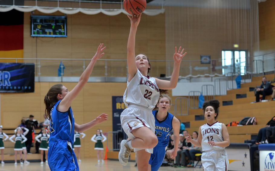 Paula Bohlen of AFNORTH goes in for a basket against Allison Wenger of Hohenfels as Tiana Rodgers and Lachelle Ellis, right, follow the action in a Division III semifinal at the DODEA-Europe basketball championships in Wiesbaden, Germany, Friday, Feb. 21, 2020. The Tigers beat the Lions 36-31 to advance to the finals.