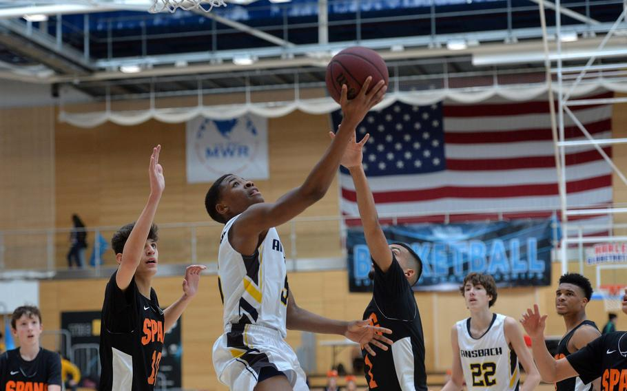 Josiah Quinland of Ansbach takes it to the hoop against Heriberto DeJesus II of Ansbach in a Division II semifinal at the DODEA-Europe basketball championships in Wiesbaden, Germany, Friday, Feb. 21, 2020.