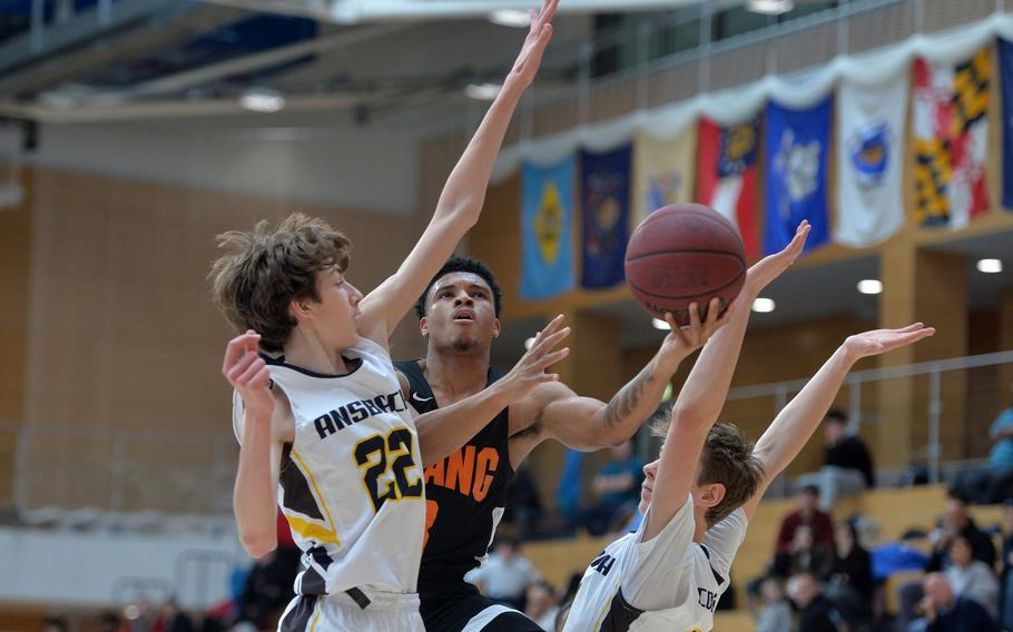 Deon Montgomery of Spangdahlem looks for the shot against Alexander Adams, left, and Lukas Morecraft of Ansbach in a Division II semifinal at the DODEA-Europe basketball championships in Wiesbaden, Germany, Friday, Feb. 21, 2020.