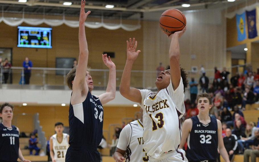 Mathew Gardner scores one of Vilseck's overtime baskets as Brandon Lee of Black Forest Academy tries to defend. The 53-49 overtime win sends Vilseck to the Division I final of the DODEA-Europe basketball championships.