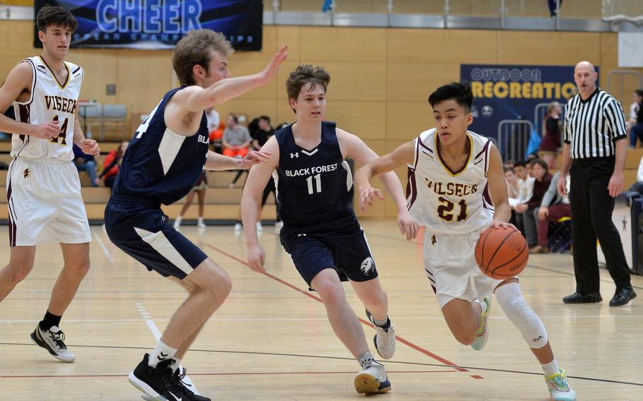 Cameron Gaetos of Vilseck drives to the basket against Markus Woodbridge, center, and Brandon Lee of Black Forest Academy in a Division I semifinal at the DODEA-Europe basketball championships in Wiesbaden, Germany, Friday, Feb. 21, 2020. Vilseck won 53-49 in overtime.