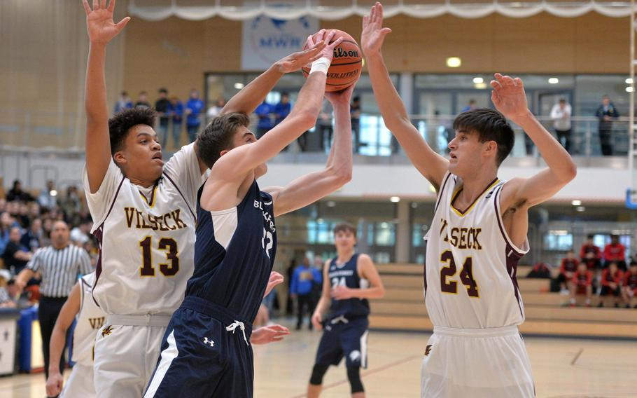 Jacob Fortune of Black Forest Academy gets between Matthew Gardner and Sean Bergosh of Vilseck to score a basket in a Division I semifinal at the DODEA-Europe basketball championships in Wiesbaden, Germany, Friday, Feb. 21, 2020. Vilseck won 53-49 in overtime.
