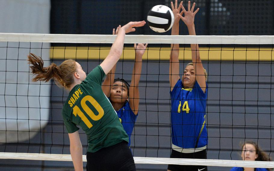 Clara Oberle of SHAPE hits past the Wiesbaden defense of Calen Prevo, left, and Alynna Palacios in a Division I match at last year's DODEA-Europe volleyball championships in Ramstein, Germany. The upcoming high school volleyball season in Europe has been canceled.