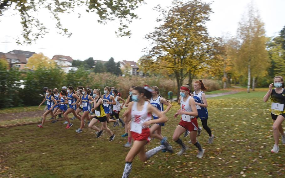 Runners in the girls large school race sprint from the starting line at the DODEA-Europe non-virtual cross country championship on Saturday, Oct. 24, 2020, at Seewoog Park in Ramstein-Miesenbach, Germany. Two girls races were held to keep runners spread out due to coronavirus, with times from both races combined into the overall results.