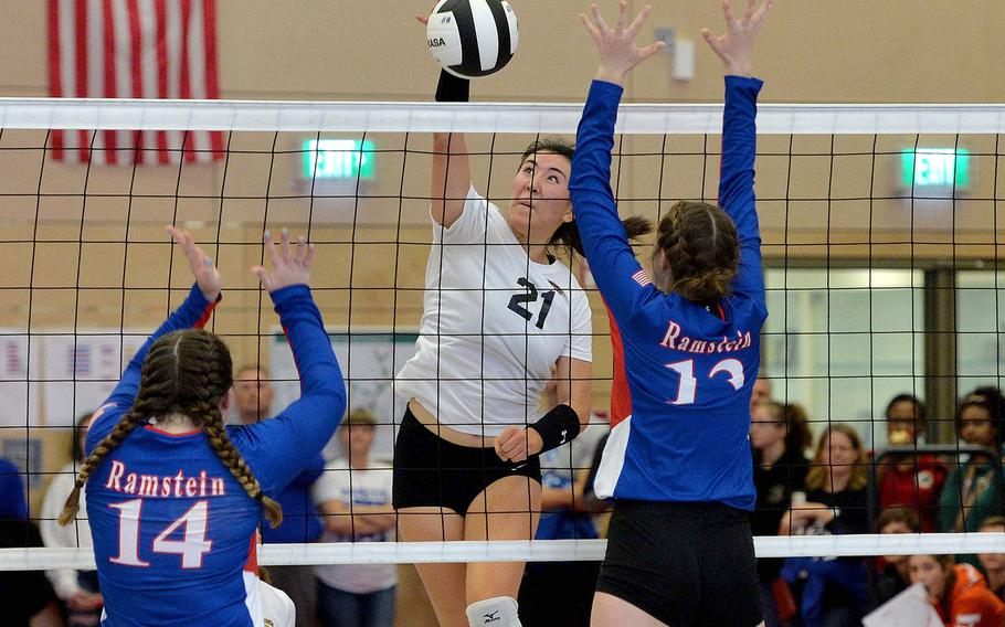 Stuttgart's Karen Kosinski slams the ball past the Ramstein defense of Lauren Szczygeil, left, and Sequoia Juhaz in the Division I final at the DODEA-Europe volleyball championships in Kaiserslautern, Nov. 2, 2019.  The two teams won't square off until at least January this season as coronavirus concerns have pushed back the start of play.