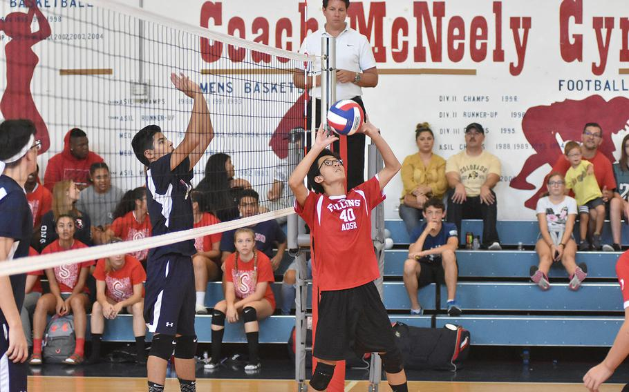 American Overseas School of Rome's Eduardo Lin sets the ball to his teammates Saturday while Aviano's Adrian Vasquez waits on the other side of the net in the Falons' 25-21, 25-20, 25-21 victory over the Saints on Saturday, Sept. 14, 2019.