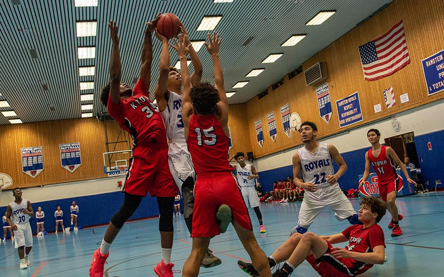 Ramstein's Jason Jones takes a shot as Kaiserslautern' Tre Dotson gets a hand on the ball during a basketball game at Ramstein High School, Germany, Dec. 17, 2019. Ramstein won the game 72-56.