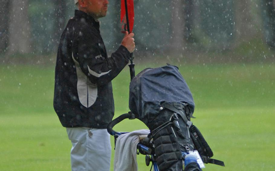 Jason Perry, an Air Force master sergeant from Ramstein, tries to stay dry during one of the many downpours during Thursday's final round of golf for the U.S. Air Forces in Europe golf championships in Ramstein, Germany.