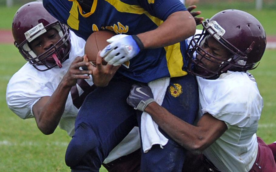 Vilseck's Dennis Thomas, left, and Xavier Scott try to drag down Heidelberg's Chris Cuthbert in a Division I game in Heidelberg on Oct. 16, 2010. Cuthbert, has been selected as the 2011 DODDS-Europe male athlete of the year.