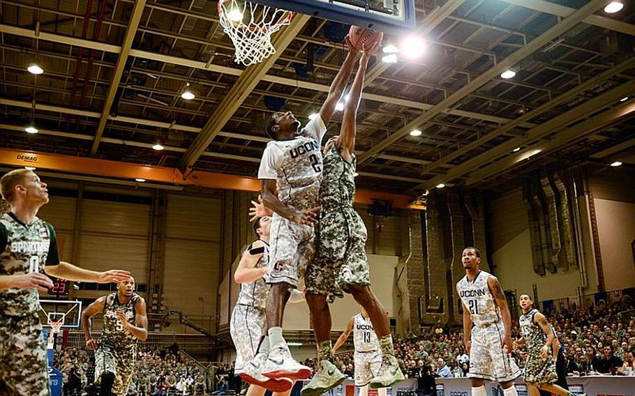 Connecticut's DeAndre Daniels blocks Michigan State's Gary Harris in the Armed Forces Classic on Nov. 9, 2012, at Ramstein Air Base, Germany. Connecticut upset No. 14 Michigan State 66-62.