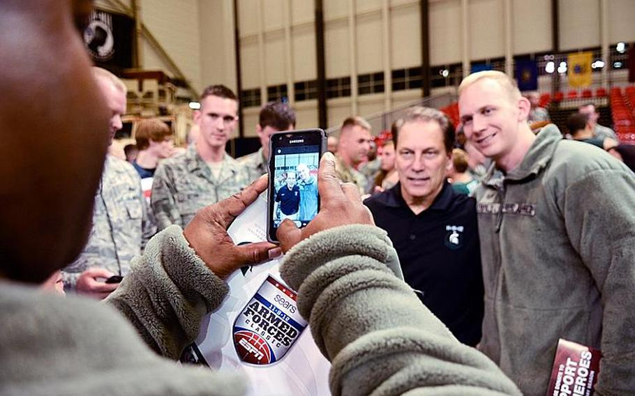 Michigan State's head coach Tom Izzo poses with a servicemember Nov. 9, 2012, after his team was upset by Connecticut 66-62 in the Armed Forces Classic at Ramstein Air Base, Germany.