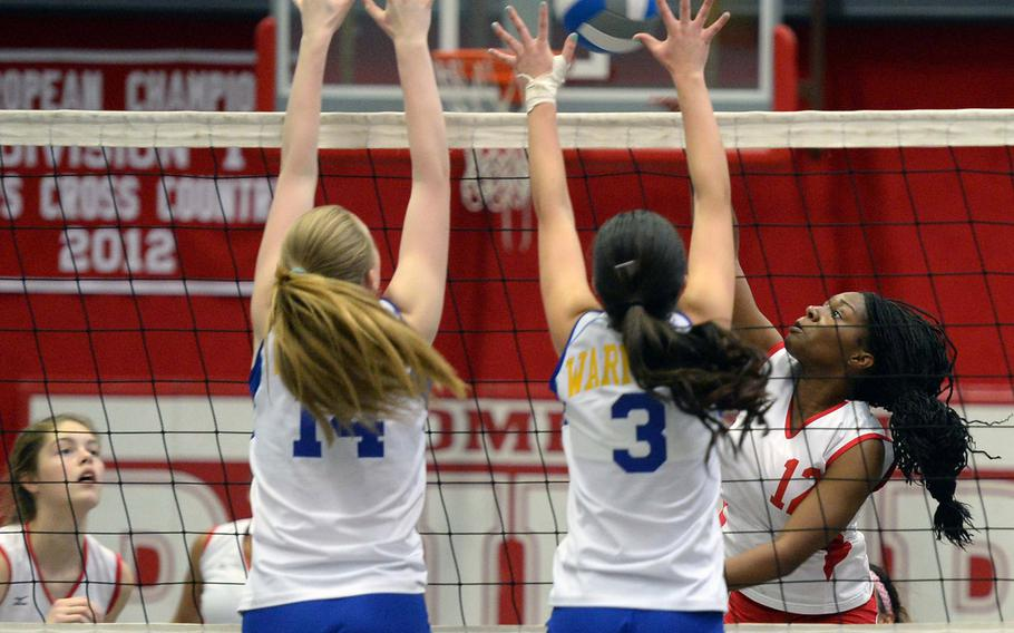 Kaiserslautern's Lashae Daniels, right, knocks the ball over the net against the defense of Wiesbaden's Brigant O' Sadnick, left, and Andriana Ibanez. Wiesbaden beat Kaiserslautern 25-20, 19-25, 25-13.