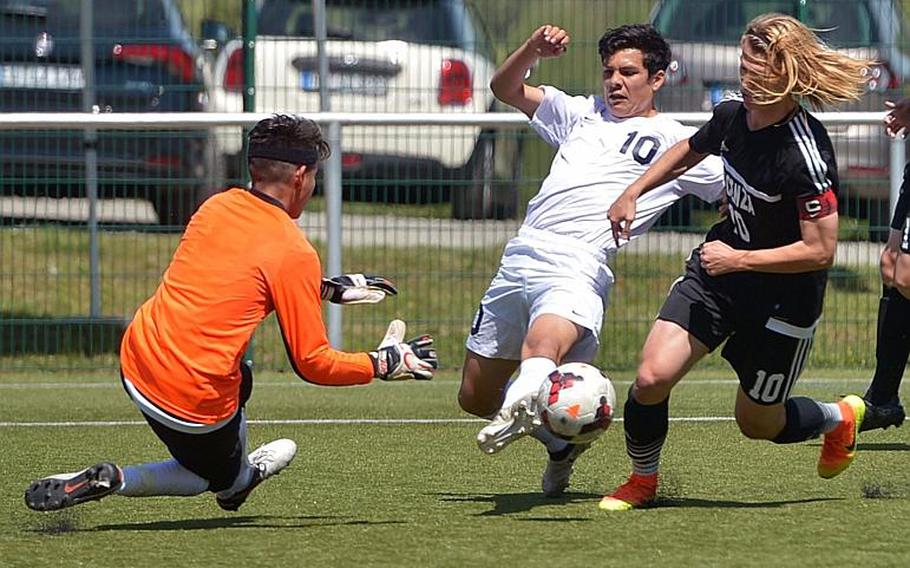 Vicenza keeper Alin Torres come out to stop Lakenheath's Tristin Reyes, with the help of teammate Nicholas Galles  in Division I action at the DODEA-Europe soccer championships in Reichenbach, Germany. Lakenheath won 2-0.