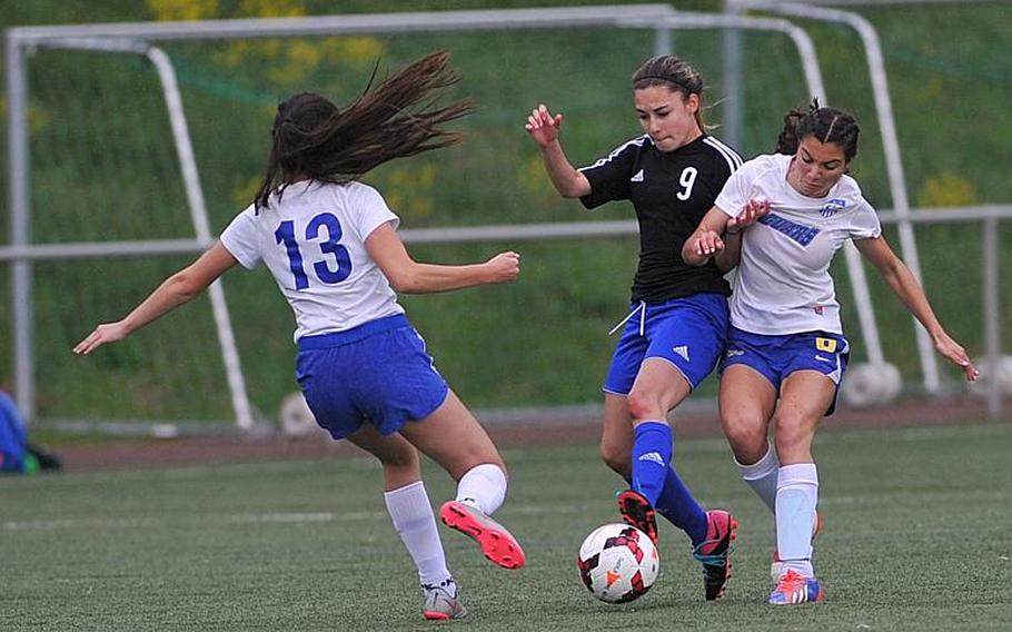 Hohenfels' Millian Comas-Ramos fights for the ball with Sigonella's Korley Jones as teammate Krystiana Wyrick comes in to help. Sigonella beat Hohenfels 3-1 in a Division III game at the DODEA-Europe soccer championships in Landstuhl, Germany.