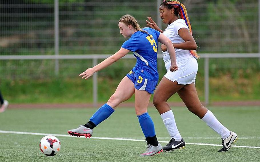 Sigonella's Violender Doke gets past Baumholder's Sierra Green to score a goal in the Jaguars' 4-0 win in a Division III game at the DODEA-Europe soccer championships in Landstuhl, Germany.