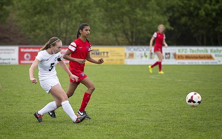 Naples' Shiloh Houseworth, left, passes the ball in front of International School of Brussels' Tasneem Amijee during the DODEA-Europe soccer tournament in Reichenbach, Germany, on Thursday, May 18, 2017. Naples won the Division I match 2-1.  MICHAEL B. KELLER/STARS AND STRIPES