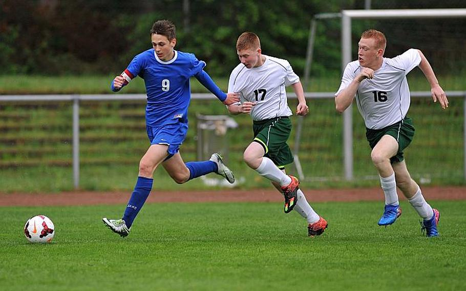 Brussels' Aljaz Urbanc gets away from Alconbury's Michael Price and Monroe Potter in a Division III game at the DODEA-Europe soccer championships in Landstuhl, Germany. Brussels won the game 3-1.
