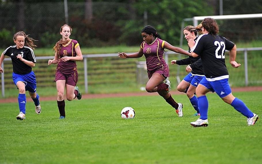 Baumholder's Laudina Gwira heads in to the box against Hohenfels' Millian Comas-Romas and Mallory Popham, as Kayleigh Leandro and Annabel Brinkmeyer follow the action at left.  Michael Abrams/Stars and Stripes