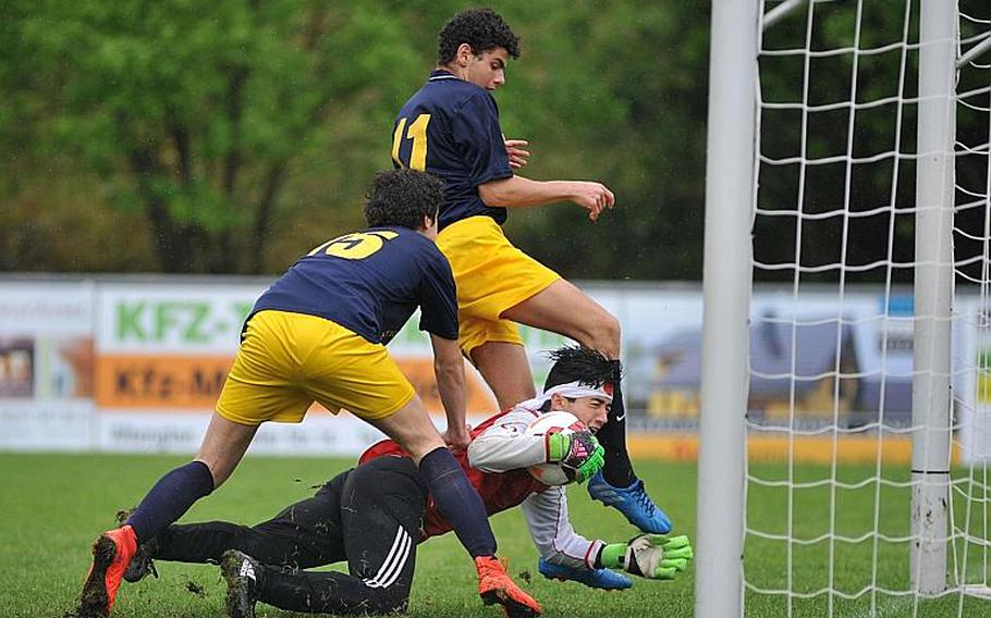 AOSR keeper Ariel Rand holds on to the ball despite the pressure by Florence's Giovanni Morescalchi and Francesco Ferragamo in a Division II semifinal at the DODEA-Europe soccer championships in Reichenbach, Germany. AOSR beat Florence 6-4 to advance to Saturday's final against Marymount.