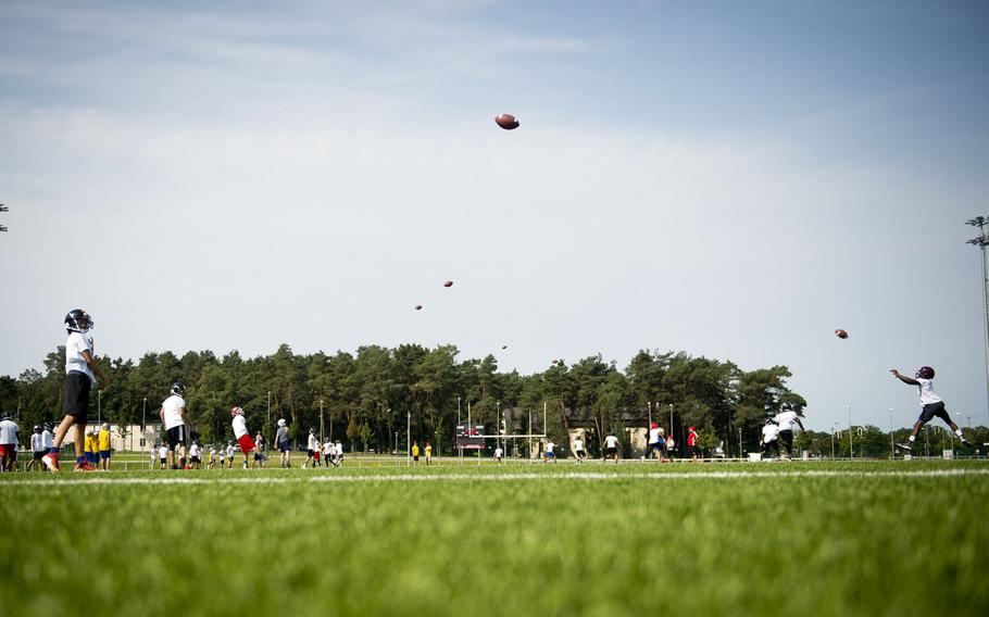Players practice passing and catching during the annual European Football Camp at Vogelweh, Germany, on Tuesday, Aug. 15, 2017.