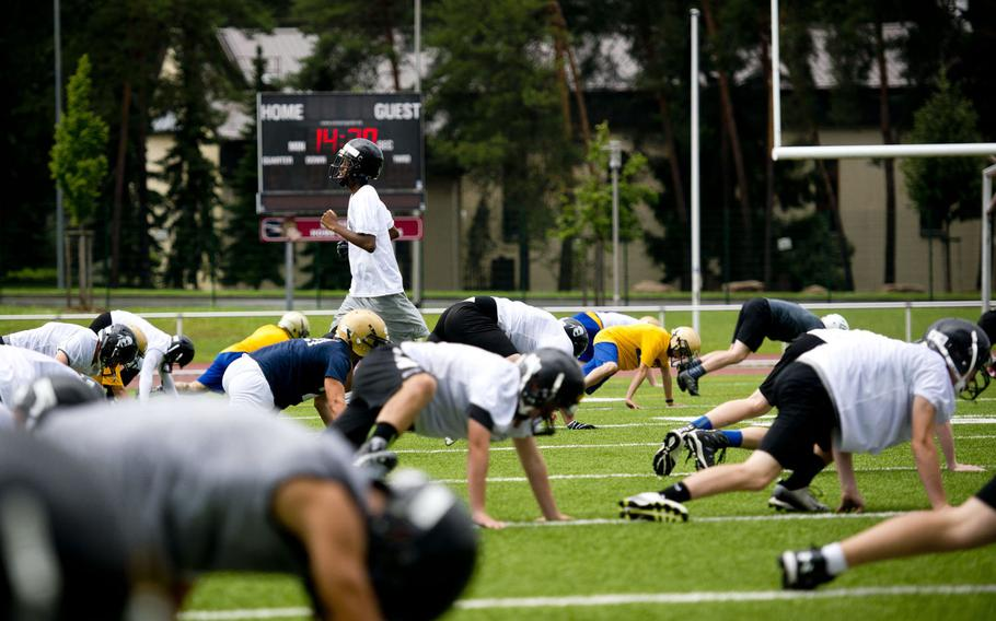 Players warm up during football camp at Vogelweh, Germany, on Tuesday, Aug. 15, 2017.