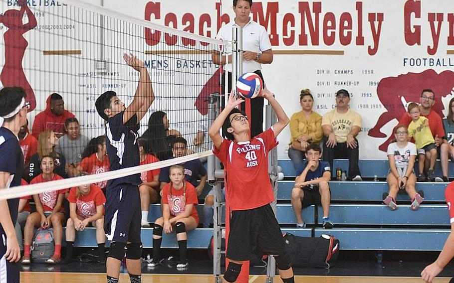 American Overseas School of Rome's Eduardo Lin sets the ball to his teammates Saturday while Aviano's Adrian Vasquez waits on the other side of the net in ta match in Aviano, Italy, Sept. 14, 2019. Boys volleyball will be played north of the Alps this coming DODEA-Europe winter sports season, replacing basketball due to coronavirus concerns.