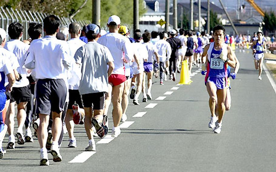 Eiji Yaguchi takes the lead going in one direction, while a pack of runners heads the other way during Sunday's race. Yaguchi placed third overall among the 2,883 men entered in the event.